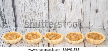 Mini apple pie over wooden background