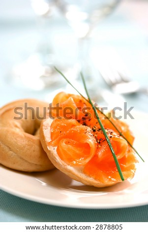 Mini bagel with smoke salmon and cream cheese served with freshly cracked black pepper.