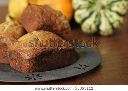 Mini banana chocolate chip loaves with fall gourds in background. - stock photo