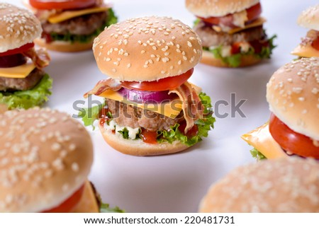 Mini beef burgers on white background,selective focus in the middle  - stock photo
