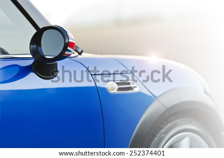Mini blue car in the sun light - stock photo