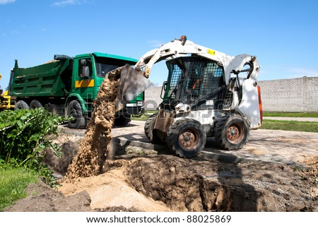 Mini Bobcat work on a street reconstruction - stock photo