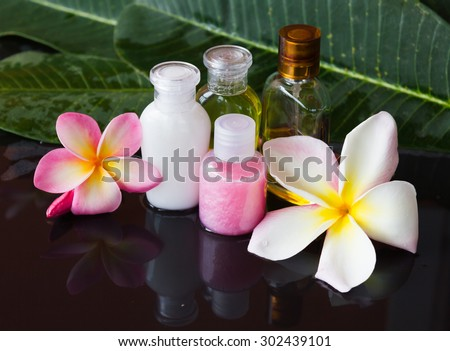mini bubble bath set decorated with flower on black background - stock photo
