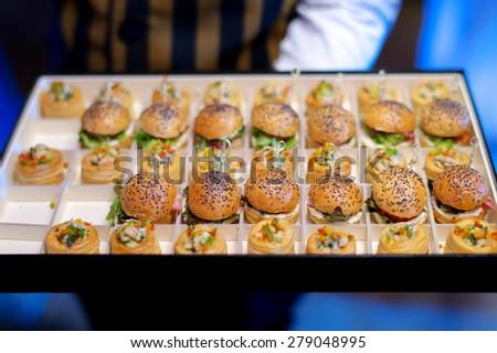 mini burger canape selection on slate platter - stock photo