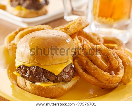 mini burgers with cheese and onion rings served with beer. - stock photo