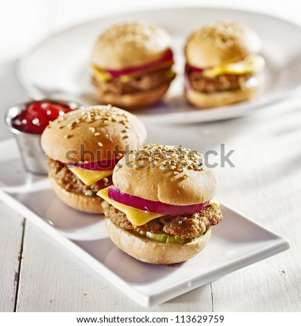 mini burgers with cheese, onion and pickle. - stock photo