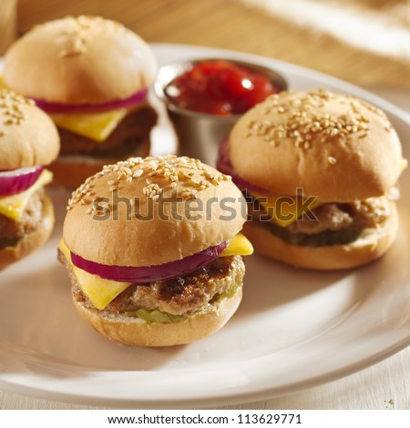 mini burgers with cheese, onion and pickle closeup with ketchup - stock photo