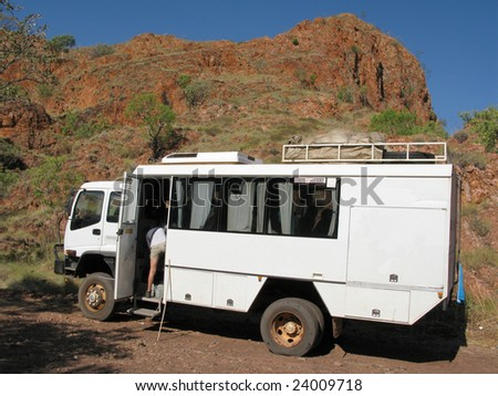 Mini bus parked under the red rock slope. El Questro Gorge, Kimberley. Western Australia. Australia - stock photo