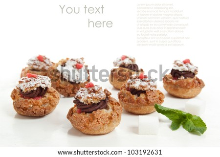 Mini-cakes with chocolate mousse served with mint over white. With sample text