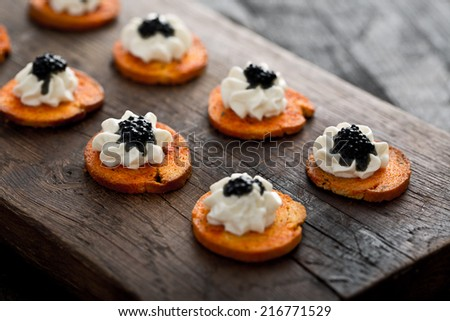 mini canapes with cream and caviar - stock photo