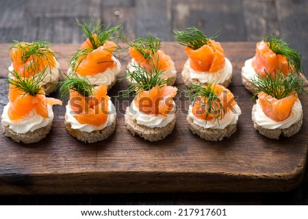 mini canapes with smoked salmon - stock photo