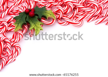 Mini candy canes making a border on a white background, Candy cane - stock photo