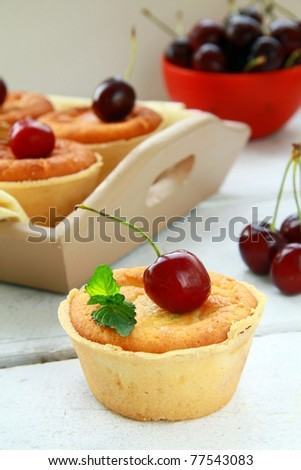 mini cheese cake with cherries and mint on a wooden table