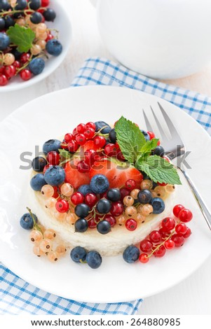 mini cheesecake with fresh berries on a plate, top view, vertical - stock photo