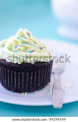 Mini chocolate cake frosted with icing and sprinkled with colourful hundreds and thousands - stock photo
