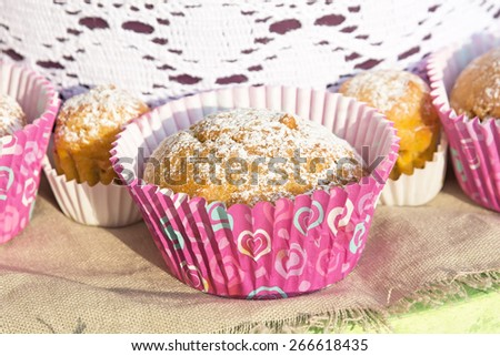 Mini cupcakes in colorful wrapper on a napkin of burlap. Picture taken at the spring fair under the open sky on a sunny day. Close-up. Shallow DOF - stock photo