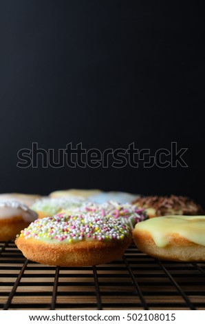 Mini doughnut cakes, decorated with a variety of sprinkles, on a black wire cooling rack with wooden table beneath.  Black chalkboard background provides copy space.