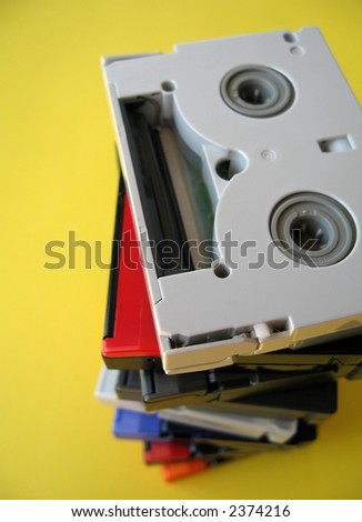 Mini DV tapes on yellow paper background. - stock photo
