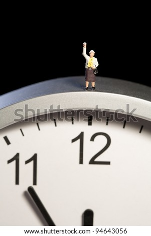 Mini figurine on a clock standing above the 12:00 position - stock photo