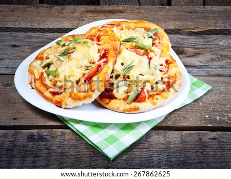 Mini focaccia with tomatoes, cheese and herbs. Shallow dof. - stock photo