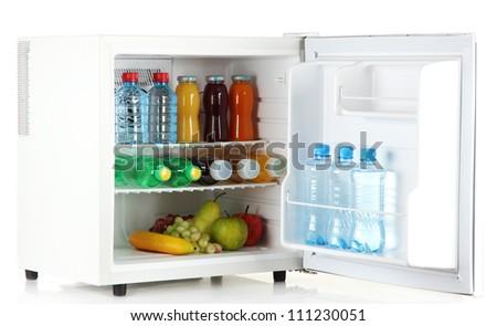 mini fridge full of bottles of juice, soda and fruit isolated on white - stock photo