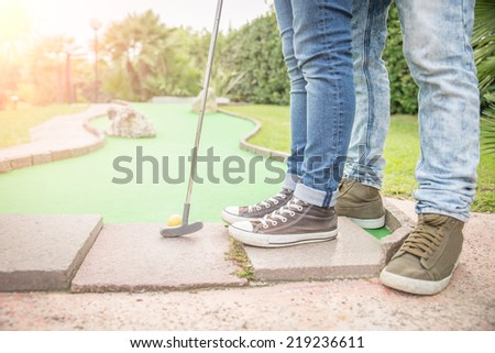 Mini golf club - Boyfriend teaching to his girlfriend how to putt - Love,couple,togetherness,vacation,leisure,sport concept - stock photo