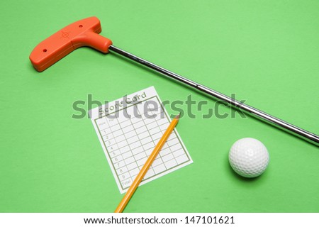 Mini golf club with score card, ball and pencil on green background - stock photo