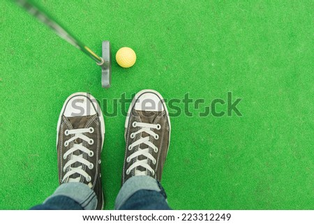 mini-golf. person with club and ball on the mini-golf court - stock photo
