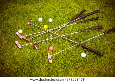 Mini golf putters and balls on the grass at mini golf club. Toned picture - stock photo
