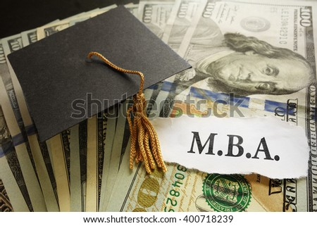 Mini graduation cap on cash with MBA paper note -- Masters of Business Administration degree concept