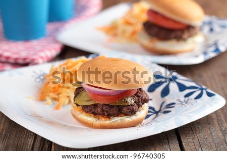 Mini hamburgers with coleslaw on paper plates - stock photo