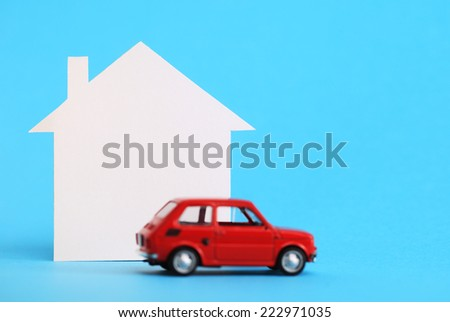 Mini house, red miniature car on blue background - stock photo