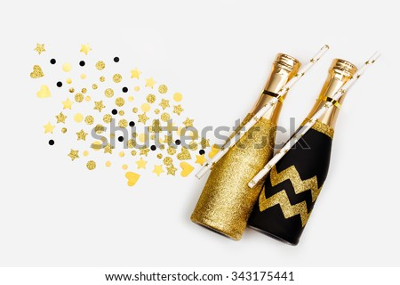 Mini individual bottles for toasting of champagne with golden confetti on white  background - stock photo