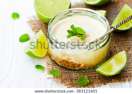 Mini  lime cheesecake in a glass pot on white wooden background