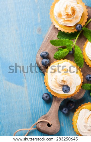 Mini lime curd tartlets with meringue. Holiday concept. Top view. Background with copy space. - stock photo