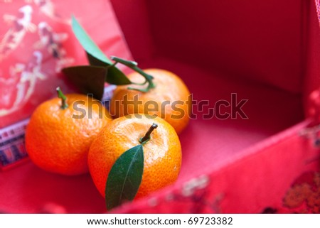 Mini mandarin oranges in a red chinese box with new  year money packet - stock photo