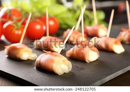 Mini mozzarella wrapped in prosciutto ham and baked  - stock photo