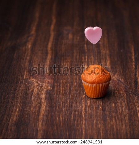 Mini muffin with a candle in the shape of a heart.Copy space. - stock photo