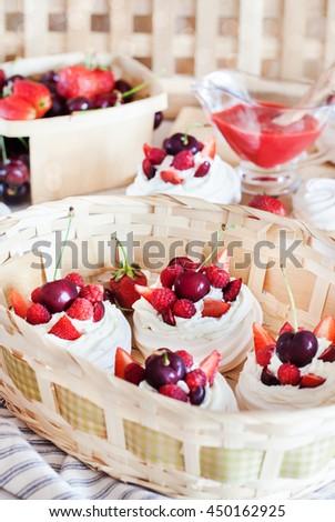 Mini Pavlova meringue cake decorated with fresh strawberry and cherry - stock photo