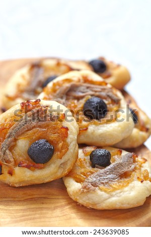 Mini pissaladieres. French pie with onion, olives and anchovies