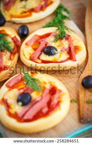 mini pizza with olives, bacon and cheese