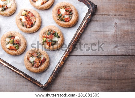Mini pizzas on a baking paper in a pan - stock photo