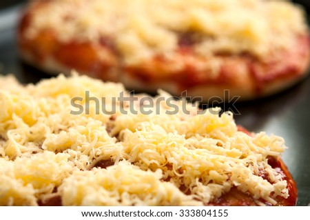Mini pizzas or small pellets covered with cheese close-up macro - stock photo