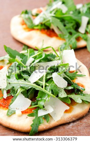 Mini pizzas with fresh rocket and shaved parmesan cheese - stock photo