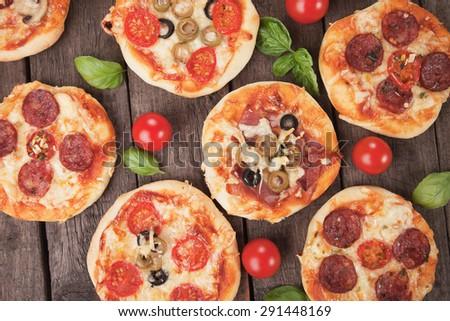 Mini pizzas with ham, salami, cheese and tomato - stock photo
