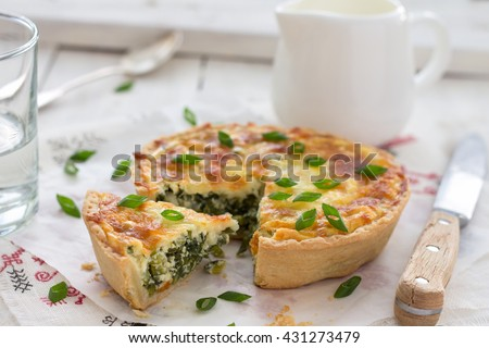 Mini quiche with green onions and cheese on a light wooden background, selective focus - stock photo