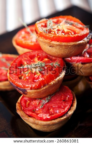 Mini quiches with cheese and tomato on black background - stock photo