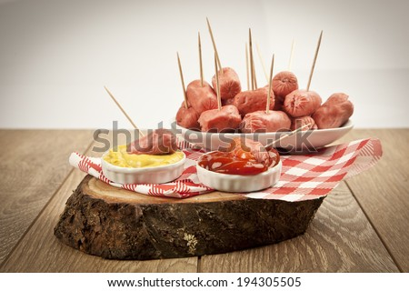 Mini Salamis Sausage in a small bowl on wooden background - stock photo