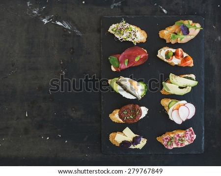 Mini sandwich set. Variety of small sandwiches on black backdrop, top view, copy space - stock photo
