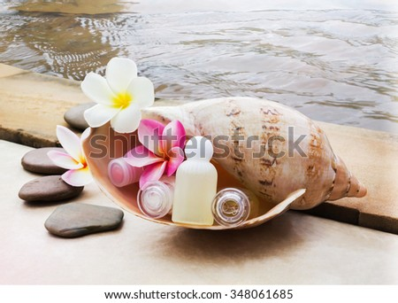 Mini set of bubble bath and shower gel decorated in sea conch shell decorated with pebble rock and flower with water background - stock photo